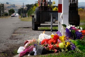 Flowers and notes of condolence continue to pile up at the police cordon around the crash site on the corner of Somerset Rd and State Highway 2 in Carterton. Photo / Sarah Ivey