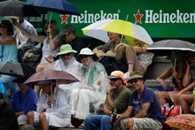 Members of the public sit in the rainduring the  Heineken Open. Photo / Sarah Ivey