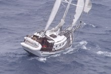 The ketch Cheval de Mer was 'rocking and rolling' in stormy seas as new communications gear was winched down to it. Photo / Northland Emergency Services Trust 