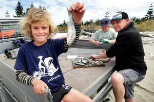 Conor White, 10, shows off a bait-fish he caught at Tolaga Bay while his dad, Mike (right) and Geoff Meade prepare a longline. Photo / Alan Gibson