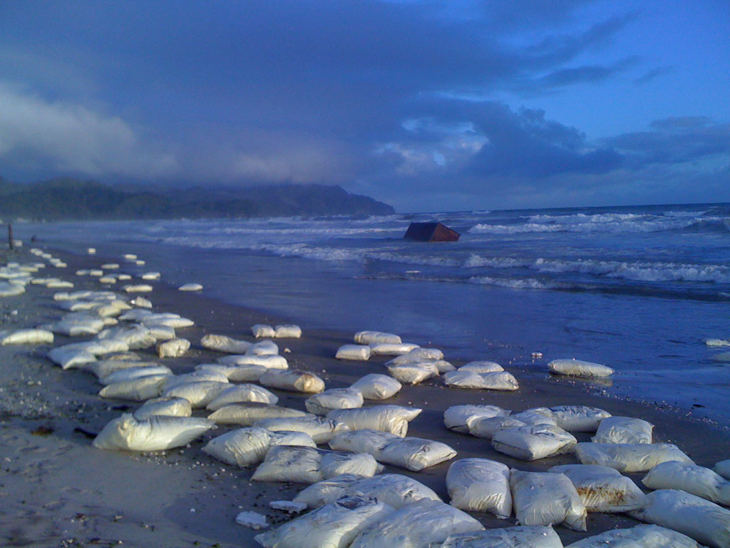 A container lies in the surf near Waihi Beach. Bags, believed to contain milk powder, line the sand. Photo / Sam Anderson