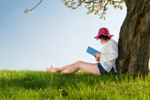 Girl sitting under a blossom tree reads her book