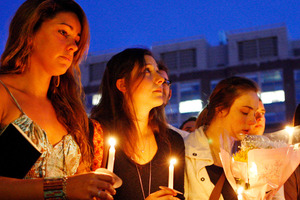 Boston University students including Tori Pinheiro, left, and Austin Brashears' girlfriend, hold a candlelight vigil on Marsh Plaza at Boston University. Photo / AP