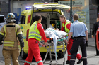 A man who set fire to himself outside the courthouse in Oslo Tuesday, May 15, 2012, where the trial of Anders Behring Breivik is taking place, is taken into an ambulance. Photo / AP