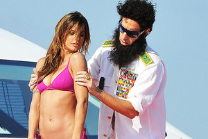 Sacha Baron Cohen's character General Aladeen rubs lotion on Elisabetta Canalis in Cannes. Photo / AP Photo / AP