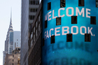 The Chrysler Building is visible behind the animated facade of the Nasdaq market site, welcoming the Facebook IPO, in New York's Times Square on Friday. Photo / AP