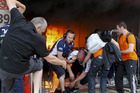 Williams's team mechanics help an injured colleague as they escape the team garage destroyed by fire. Photo / AP