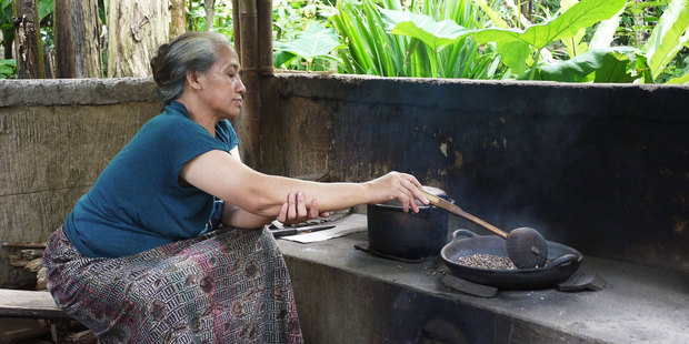 A woman roasts beans to make kopi luwak, after they've been conveniently processed by the Asian palm civet. Photo / Kieran Nash
