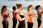 Yoga instructor Kris McIntyre (centre) leads a yoga session on the beach at Kingscliff. Photo / Supplied