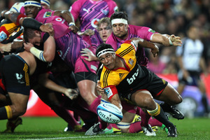Chiefs flanker Tanerau Latimer clears the ball under pressure during last night's victory over the Bulls in Hamilton. Photo / Getty Images