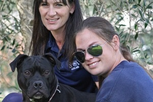 SPCA staff Lori Davis (left) and Katie Wright with Coecoe - a far cry from the sick, malnourished dog which was rescued 10 months ago. Photo / SPCA