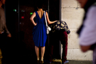 A girl rubs a man's back while he vomits. Photo / Dean Purcell