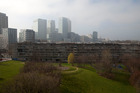 The towers of the Canary Wharf business and shopping district rise beyond the Robin Hood Gardens estate in London's borough of Tower Hamlets. Photo / Bloomberg