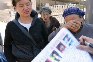 Family members with photos of their missing relatives in Nanmen. Photo / AFP