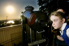 Students in Sydney look through a telescope to watch the transit of Venus. Photo / AP
