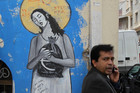 An man talks on his mobile phone in front of graffiti depicting an angel with a bag of euros, in Athens. Recent polls suggest rising support for the country's international rescue package. Photo / AP