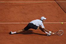 Novak Djokovic of Serbia slides to the net as he returns in his first-round match against Potito Starace of Italy at Roland Garros. Photo / AP