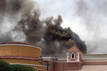 Family members of victims react with grief after the fire took hold of the Villagio Mall. Photo / AP