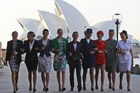 Australian designer Martin Grant, centre, walks with models wearing the Qantas uniforms old to the current. Photo / AP