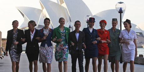 Australian designer Martin Grant, centre, walks with models wearing the Qantas uniforms old to the current.