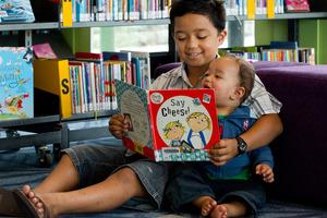 Terenui Natua, 8, reads to his little brother Arani, 1, at the Tupu Youth Library, Flat Bush. Photo / Brett Phibbs