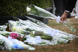 A family member lays a flower in remembrance with those that gathered at Hagley Park a year after the quake. Photo / NZ Herald