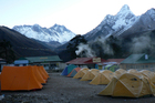 Early morning at the camp at Tengboche, with Mt Everest peering over the ridge at left. Photo / Jim Eagles