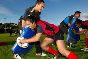 All Blacks wing Hosea Gear holds the tackle bag as Rowena Tapasu, 13, from Onehunga High School takes part in a surprise training session yesterday.  Photo / Richard Robinson