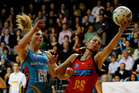 Irene van Dyk gets the ball under pressure from Storm Purvis.  Photo / Christine Cornege