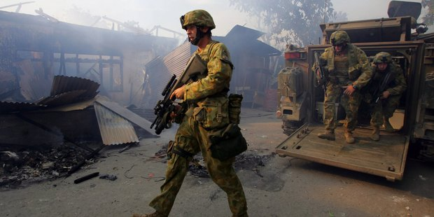 Australian peacekeeping soldiers walk through the smoke from an entire block of burning homes in East Timor. Photo / AP.