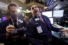 Trader Gregory Rowe, left, and specialist Peter Giacchi work on the floor of the New York Stock Exchange. Photo / AP