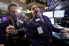 Trader Gregory Rowe, left, and specialist Peter Giacchi work on the floor of the New York Stock Exchange. Photo /