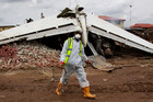 A rescue worker walks past the wreckage of the plane in Lagos, Nigeria. Photo / AP