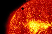 This image provided by NASA shows the Solar Dynamic Observatory's ultra-high definition view of Venus, black dot at top centre, passing in front of the sun.