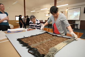 Rangi Te Kanawa inspects an old cloak belonging to Audrey Harris (on her left) at the NorthTec marae in Raumanga. Photo / APN