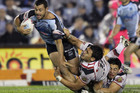 Jason Bukuya of the Sharks is tackled by the Warriors defence. Photo / Getty Images.