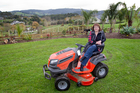 Sandra Roberts and her ride-on lawnmower at home in Waitoki. Photo / NZ Herald
