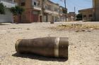 A shell is seen in a street at a residential area of Talbisah in Homs city Syria. Photo / AP
