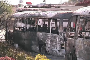 Buses burned in overnight fighting in Damascus. Photo / UN