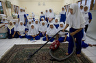 Women learn to vacuum in Jakarta in 2006 at a training centre that sends domestic workers abroad. Above right, the Auckland Ferry Building, by Henry Winkelmann in 1913. Photo / Magnum, Auckland Libraries