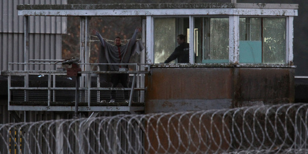 Prisoners gesture from an observation tower at the maximum security Paremoremo prison. One of them is Aaron Forden, nicknamed 'Houdini' for his many escapes. Photo / Getty