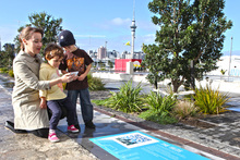 Using the new QR codes and signs installed by Waterfront Auckland from The Cloud to the silos at Wynyard Quarter. Photo / Supplied