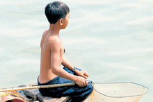 A Vietnamese boy fishes for turtles on the Saigon River, just metres from the streets of Ho Chi Minh City. Photo / Bay of Plenty Times