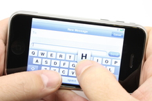 Texting on a touch screen phone turned sideways.