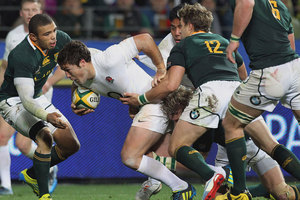 England's Brad Barritt, center, attacks as South Africa's Bryan Habana, left, and teammates defend during their Rugby Test match against South Africa. Photo / Getty Images.