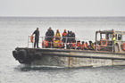 A barge delivers some of those rescued to Christmas Island. Photo / Getty Images