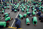 Children from Mt Roskill and Mt Eden Primary Schools practise the 'drop, cover and hold' technique. Photo / Steven McNicholl