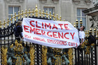 Protesters from the Climate Siren group hang a banner from the gates of Buckingham Palace. Photo / AP