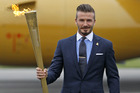 David Beckham with the Olympic torch. Photo / AP.