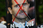 A protester holds up a poster of Syrian President Bashar al-Assad with cross mark over it during a protest rally against Assad's regime outside. Photo / AP